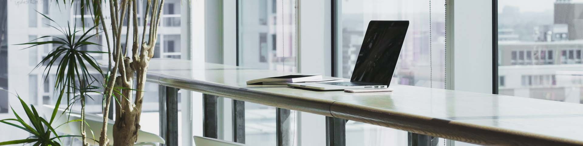 bg-laptop-sitting-on-long-desk-by-large-windows